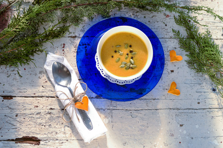 Pumpkin cream soup in a bowl  on a vintage plate with seeds and spices photo