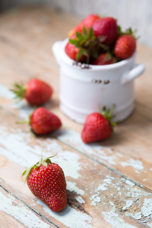 White clay pot with strawberries on a woodeb background, table shabby chic photo