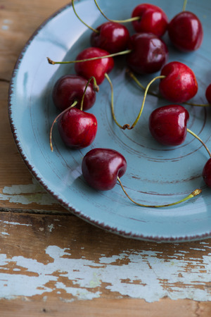 Blue ceramic shabby plate full with dark red juicy cherries