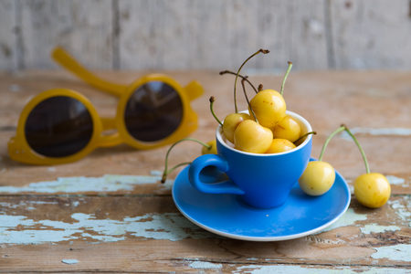 Blue tea cup full with yellow juicy cherries