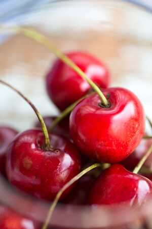 summer juicy berries - red cherries in a glass bowl, close up on a wooden table Stock Photo