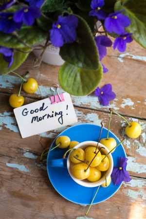 Blue tea cup full with yellow juicy cherries with a good morning note card on a wooden table with violets Stock Photo