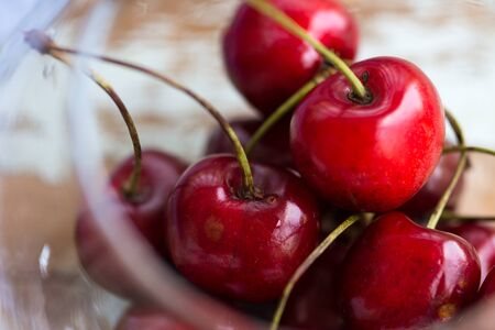 red cherries in a glass bowl, close up on a wooden table