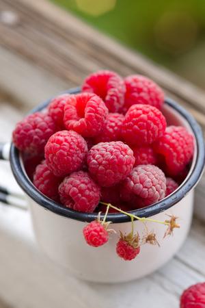 enamel: enamel vintage cup full of raspberries, summer taste Stock Photo