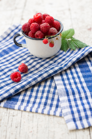 enamel vintage cup full of raspberries, summer taste on a blue striped tea towel Stock Photo