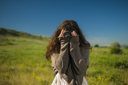 a brown-haired girl covered her face with her hands in nature against a blue sky Stock Photo
