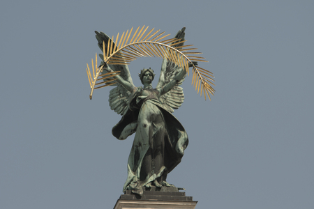 bronze sculpture genius with gold Palm branch and wings on the roof of the opera house in Lvov. blue sky background