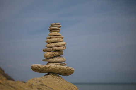 balancing pyramid of stones on a large stone on the seashore