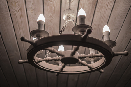 lamp with bulbs, chandelier in the form of a wheel, wooden ceiling Stock Photo