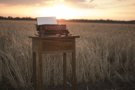 typewriter on a walnut bedside table in a wheat field at sunset