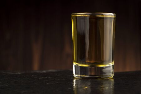glass of whiskey on the table on wooden background