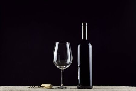 wine bottle, glass and corkscrew on a black background