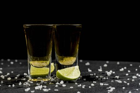 tequila is poured into two glasses and salt and lime