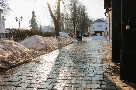 Street paved large natural stone blocks on sunny day in winter