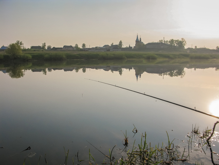 Fishing for bait in a quiet magical spring morning from the shore of the lake.