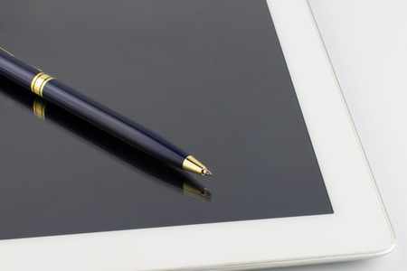 Tablet computer and a modern metal pen on a white background.