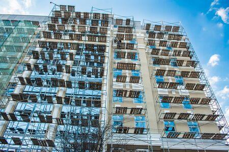 Echafaudage sur la rénovation de la façade de verre lumineux jour ensoleillé ciel bleu.