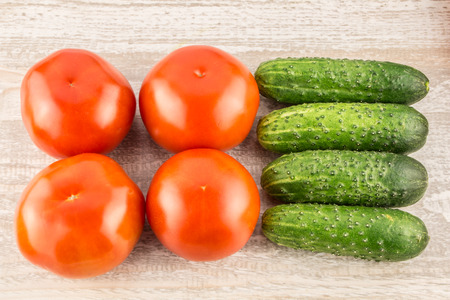 Tomatoes and cucumber on light natural wooden background