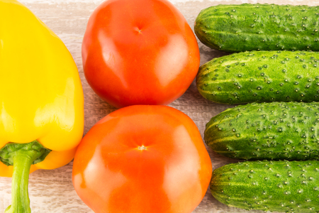 red onions: Tomatoes, yellow bell pepper and cucumber on light natural wooden background Stock Photo