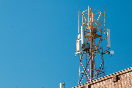 Communication tower on the roof of a building against the blue sky