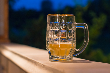 beer mug on a stone railing against the evening sky, sunset before the onset of a summer.