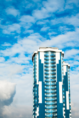 High-rise building with a glass facade against a bright blue sky with figured clouds.
