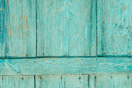 Old blue wooden door with old rusty nails and peeling paint background.