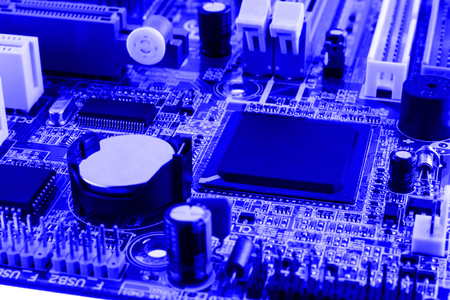 Electronics components on modern PC computer motherboard with RAM connector slot and CPU Socket.