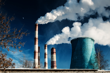 large pipes in the industrial zone with voluminous white smoke against the background of a deep blue sky with the moon