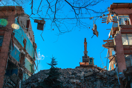 Urban scene. Dismantling of a house. Building demolition and crashing by machinery for new construction. Industry. 写真素材