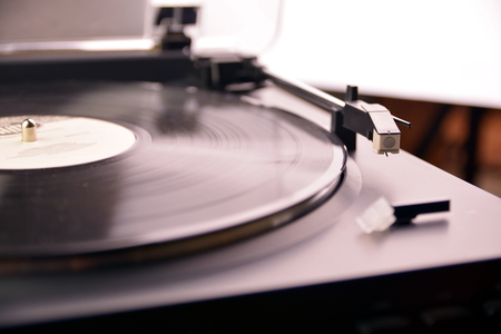 Turntable vinyl record player is playing music.