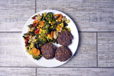 Meat patties with vegetables on a white plate on a gray background. Zdjęcie Seryjne