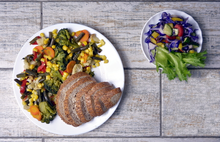 Vegetable sala with bread and vegetarian salad on gray background.