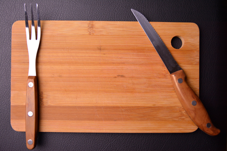 wooden board in the kitchen with fork and knife.