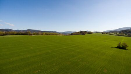 Aerial View. Panorama over a green grassy in mountains. Archivio Fotografico