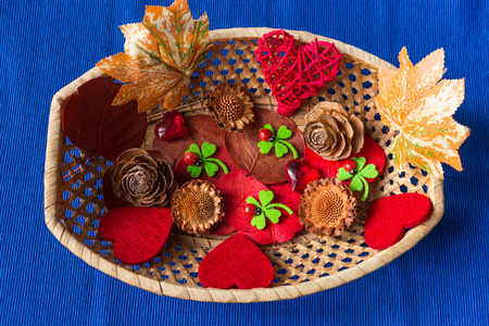 potpourri: Red hearts, dried foliage and pine cone. Christmas decoration on blue background Stock Photo