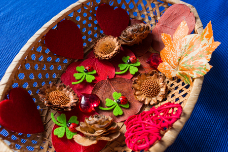 nutshells: Red hearts, dried foliage and pine cone. Christmas decoration on blue background Stock Photo