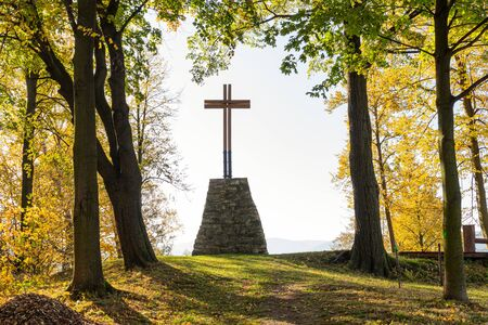 Wooden Christian religious cross on the background of green trees Фото со стока