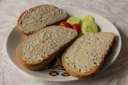 A modest breakfast in the form of three breads with fish spread and as a side dish are small tomatoes and sliced cucumber. Everything ready on a plate to eat.