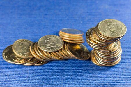 Money coins in a pile on blue background.