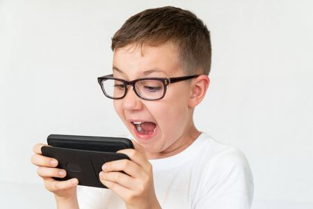 School boy looks handsome smartphone video, in glasses, dressed in white shirt, on white background, screams in fright