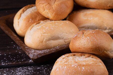 Panini nel cestino del pane su uno sfondo di legno, chiave bassa Archivio Fotografico