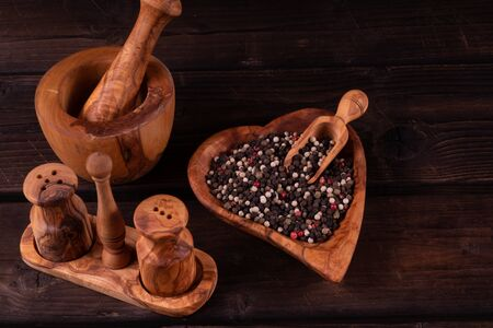 wooden mortar with small wooden spoon for spices, pepper, low key, olive wood, rustic.