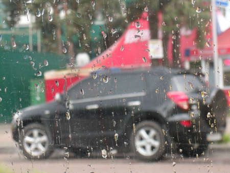 Raindrops on car glass with black car on the background