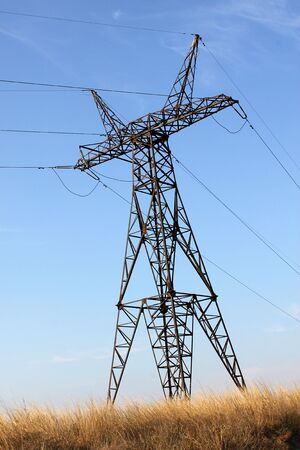 electricity pillar in a field over blue sky photo