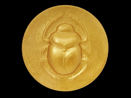 scarab: golden color egyptian amulet with image of scarab