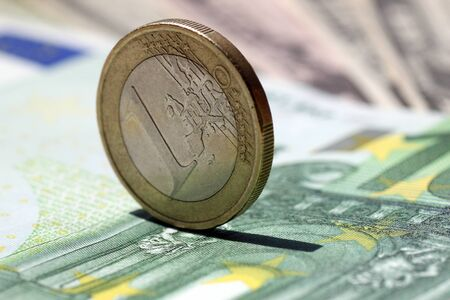 one hundred euro banknote: One euro coin on a one hundred euro banknote