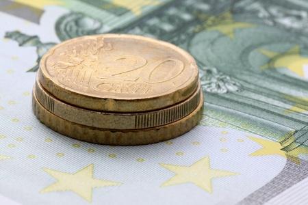 one hundred euro banknote: cerca de la pila de monedas de euro el billete de cien euros