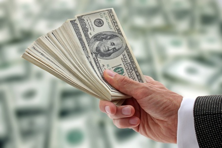 mano con dinero: mano de empresario sosteniendo d�lares Foto de archivo