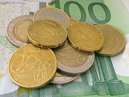 one hundred euro banknote: heap of coins on one hundred euro banknote Stock Photo